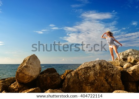 Girl after a shipwreck sitting on the rocks