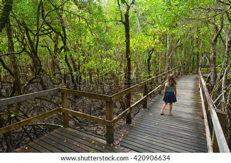 Girl (age 6) walks on a path in Daintree National Park in the tropical north of Queensland, Australia that was founded in 1981and became a World Heritage Site. - stock photo