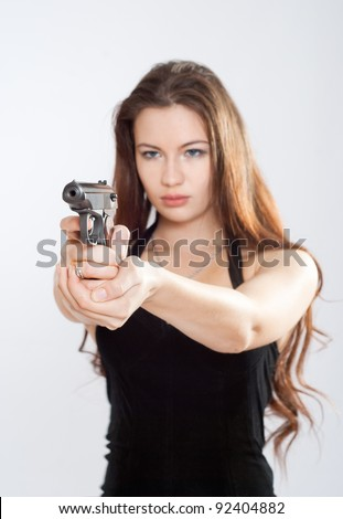 Girl aiming a gun, arms outstretched - stock photo
