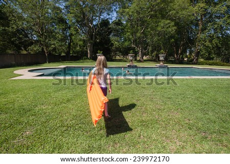 Girl Air-Matt Pool Summer Young girl walking to swimming pool with orange air-matt summertime at home. - stock photo