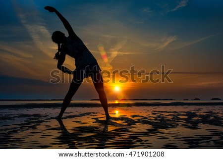 Girl alone Fitness practice in a sunrise at the beach in late summer