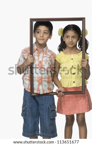Girl and a boy holding an empty picture frame