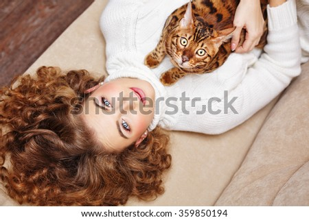 Girl and Bengal cat home. Home comfort. Girl and a cat lying on the couch. - stock photo