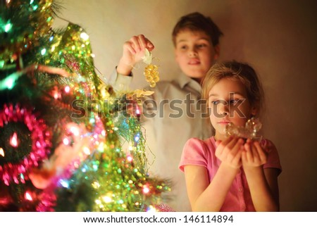 Girl and boy decorated Christmas tree by glass toys at evening. Boy holds grape and girl holds horse. Focus on girl. - stock photo