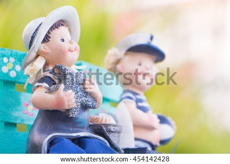 Girl and boy doll in the garden: Shallow dept of fleld