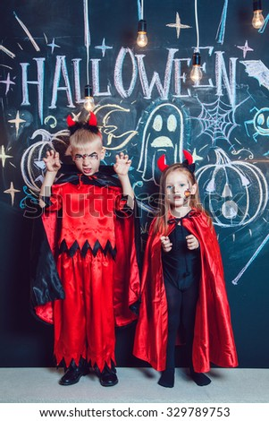 Girl and boy, dressed up in Halloween costumes, show emotions of witches . Halloween party with group children.