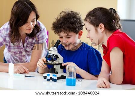 Girl and boy examining preparation under the microscope - stock photo