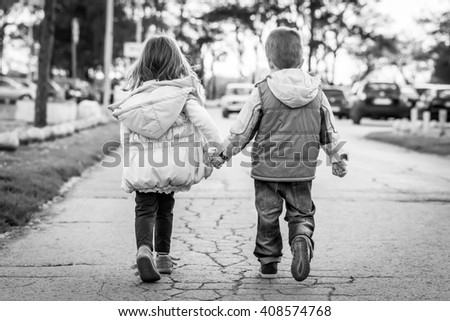 girl and boy hand in hand  running , black and white - stock photo