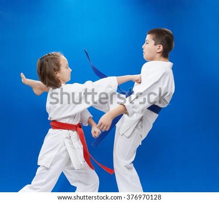 Girl and boy in karategi train the punch arm and kick leg - stock photo