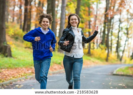Girl and boy jumping, running outdoor - stock photo