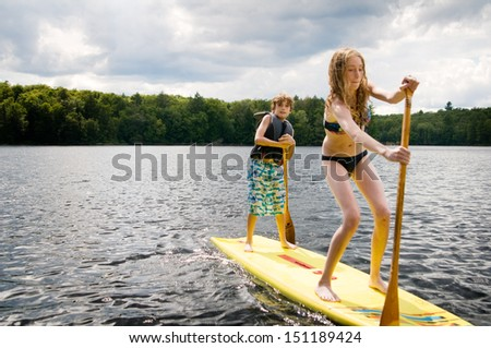 girl and boy on a stand up paddle board - stock photo