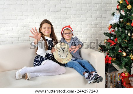 Girl and boy on the couch with a clock in his hands near the Christmas tree - stock photo