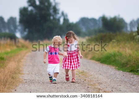 Girl and boy playing in the rain. Kids play outdoor by rainy weather in fall. Autumn fun for children. Toddler kid and baby walk in the garden. Summer shower. Brother and sister run holding hands. - stock photo