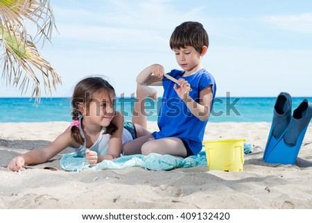 girl and boy playing on the beach