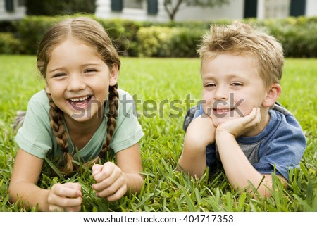 girl and boy smiling lying on the grass