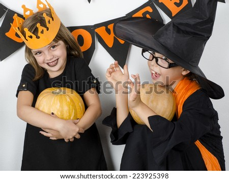 girl and boy  wearing halloween costume with pumpkin  - stock photo