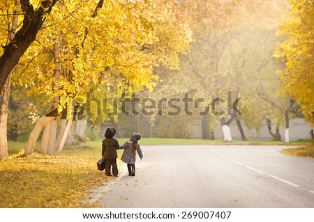 Girl and boy with a suitcase walking along the road, discussing the itinerary