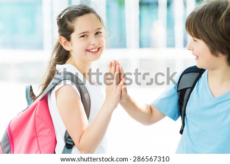 Girl and boy with backpacks  - stock photo