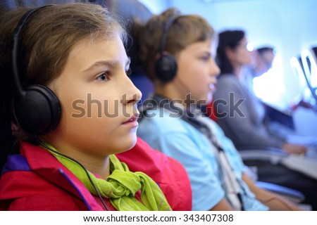 girl and boy with headphones on an airplane - stock photo