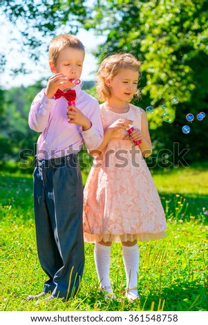 girl and boy with soap bubbles in the park - stock photo