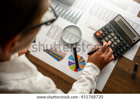 Girl and business accessories (notebook, calculator, planchette, tablet, fountain pen, glasses) and graphics, tables, charts on white sheets on office desk. Soft focus, lights effects.