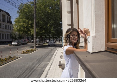 Girl and city. There is a picture of an young woman is on the streets.
