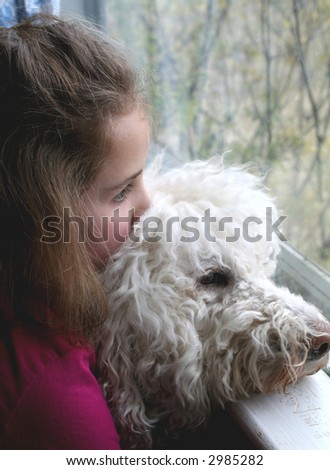 Girl and dog looking out of a window