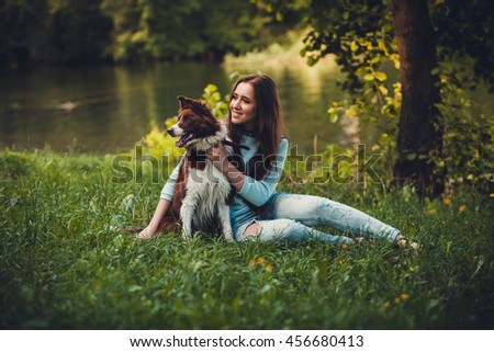 girl and dog sitting on the grass in the park near the water
