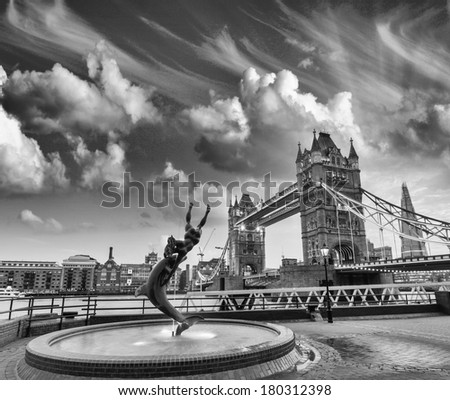 Girl and Dolphin statue against Tower bridge on a cloudy day. Black and white processed