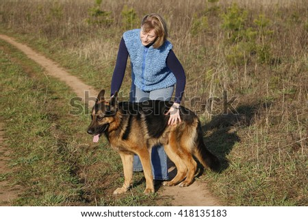 Girl and German shepherd dog on the field