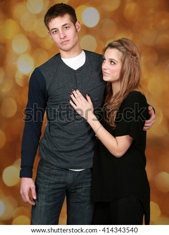 girl and guy fashion models on gold bokeh background - stock photo