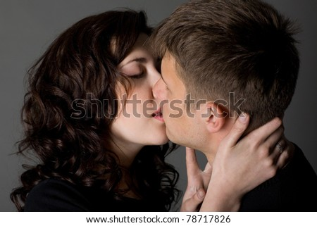 Girl and guy kiss on a gray background. - stock photo
