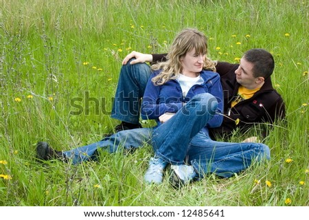 Girl and guy lay on a grass and look against each other - stock photo