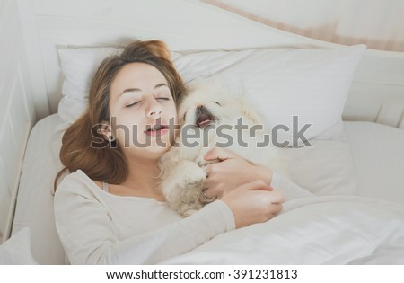 Girl and her dog in the bed.