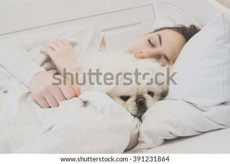 Girl and her dog in the bed. - stock photo