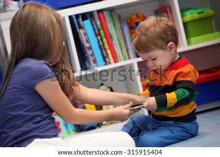 girl and her little brother crying and arguing with a digital tablet computer - stock photo
