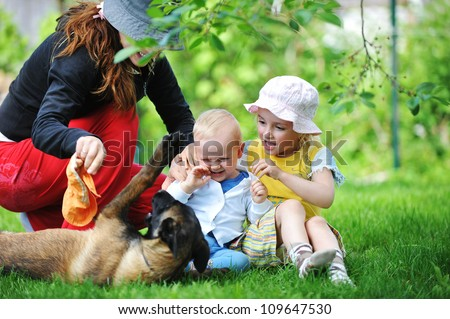 girl and her little brother playing with  dog on  grass