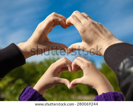 girl and her mother show sign of heart with their hands outside on sunny spring day - stock photo