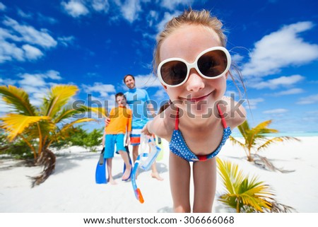Girl and her with snorkeling equipment enjoying beach vacation - stock photo