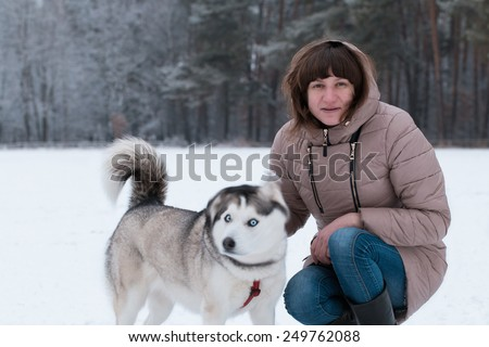Girl and Husky. Girl playing with Siberian Husky in field. Fresh snow covered field.