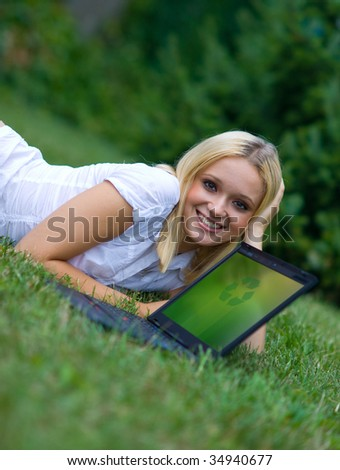 girl and laptop with recycle sign on the grass - stock photo