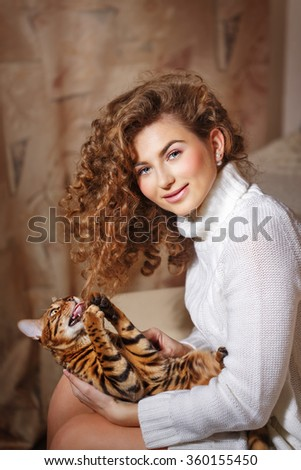 Girl and leopard cat home. Home comfort. Cat playing with curly hair girl. - stock photo