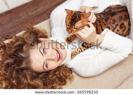 Girl and leopard cat home. Home comfort. Girl and a cat lying on the couch. Girl scratching cat. - stock photo