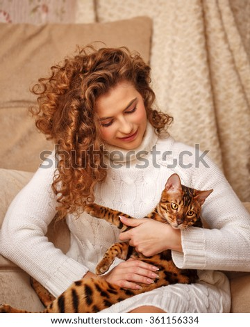 Girl and leopard cat home. Home comfort. Girl hugging cat. - stock photo