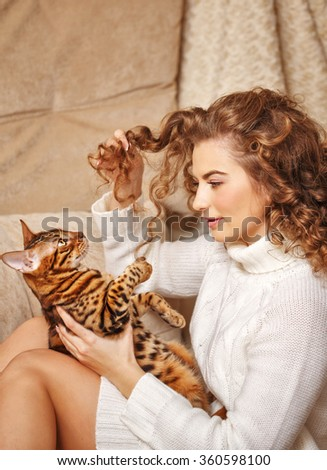 Girl and leopard cat home. Home comfort. The girl plays with cat hair. - stock photo