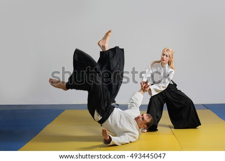 girl and  man demonstrate  techniques of Aikido.