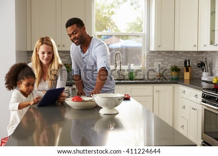 Girl and mixed race parents use tablet computer in kitchen - stock photo