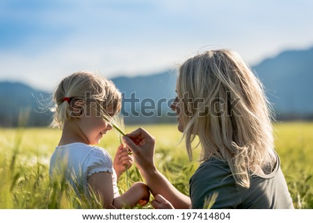 Girl and Mommy in a wheat field A little girl playing with mommy in a wheat field - stock photo