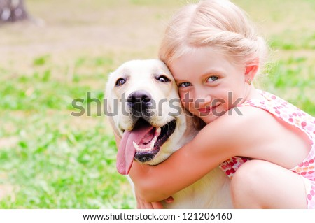 girl and she lablador, hugging in the park lying on the grass - stock photo
