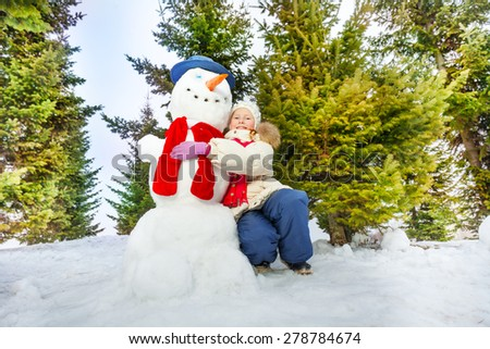 Girl and snowman with scarf together in forest - stock photo